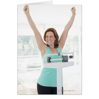 Successful weight loss. Happy woman weighing Card
