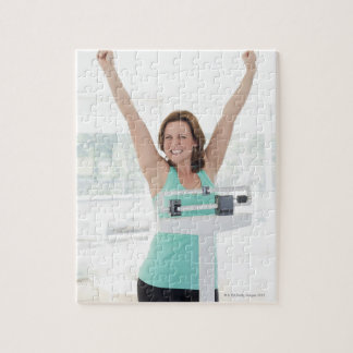 Successful weight loss. Happy woman weighing Jigsaw Puzzle