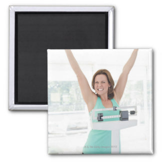 Successful weight loss. Happy woman weighing Magnet