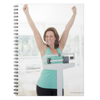 Successful weight loss. Happy woman weighing Notebook