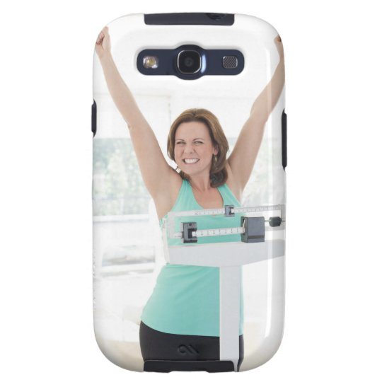 Successful weight loss. Happy woman weighing Samsung Galaxy S3 Case