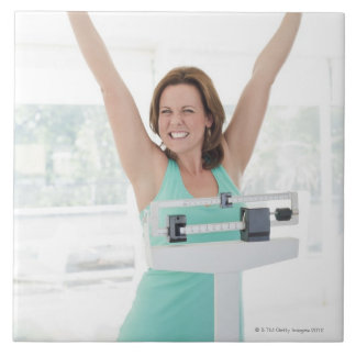 Successful weight loss. Happy woman weighing Tile