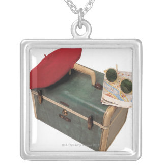Suitcase , beret , map , and sunglasses silver plated necklace