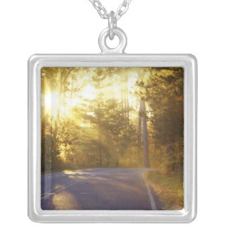Sun bursts through the forest onto roadway at square pendant necklace