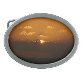 Sun detrás del paisaje marino del naranja de las hebillas de cinturón ovales