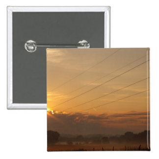 Sun emerge sobre las nubes sobre pasto de niebla pin cuadrado