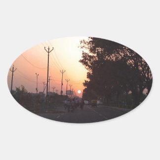 Sun en el camino en la puesta del sol pegatina ovalada