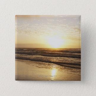 Sun on horizon over ocean button