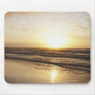 Sun on horizon over ocean mouse pad
