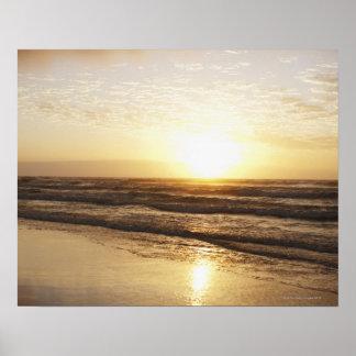 Sun on horizon over ocean poster