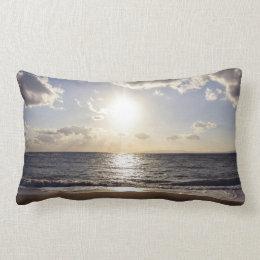 Sun pierces the blue sky on a deserted beach lumbar pillow
