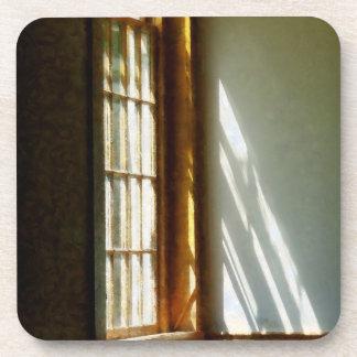 Sun que fluye a través de ventana posavasos de bebidas