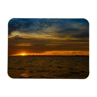Sun setting down behind the city rectangular photo magnet