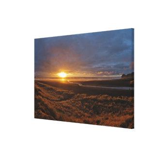 Sun setting over Tasman Sea and Piha Beach, West Canvas Print
