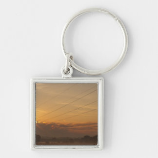 Sun surfaces above the clouds over foggy Pasture Keychain