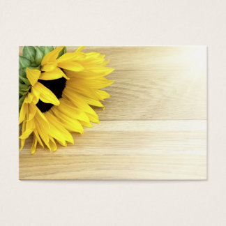 Sunflower laying on a wooden table business card