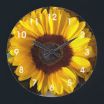 """Sunflower Wall Clock<br><div class=""""desc"""">This home decor item features a photo of a cheerful yellow and brown sunflower.  It&#39;s sure to brighten up any room.</div>"""