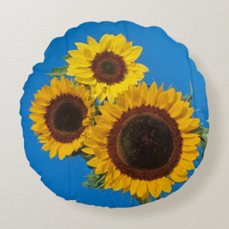 Sunflowers against blue fence round pillow