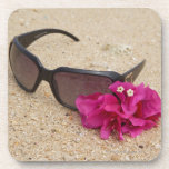 Sunglasses and bougainvillia flowers on coral beverage coaster
