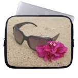 Sunglasses and bougainvillia flowers on coral laptop sleeves
