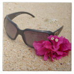 Sunglasses and bougainvillia flowers on coral tile