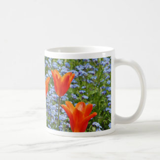 Sunny orange tulips in blue floral meadow print coffee mug
