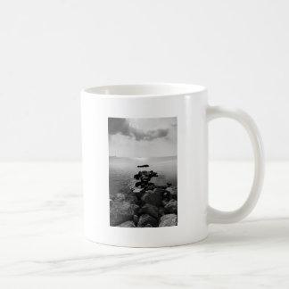 Sunrays dispersados por las nubes sobre la bahía taza de café