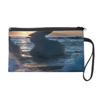 Sunrise and iceberg formation on the beach wristlet purse