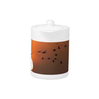 Sunrise with flocks of flying cranes teapot