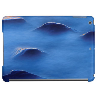 Sunset on rocks protruding through foamy water iPad air cover