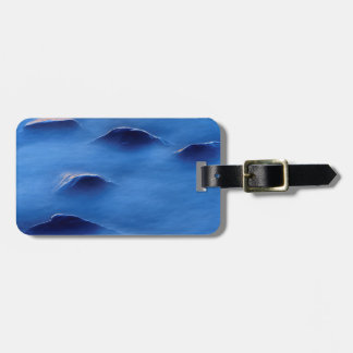 Sunset on rocks protruding through foamy water luggage tag