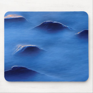 Sunset on rocks protruding through foamy water mouse pad
