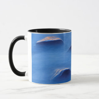Sunset on rocks protruding through foamy water mug