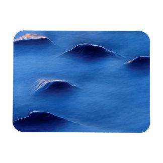Sunset on rocks protruding through foamy water rectangular photo magnet