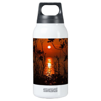 Sunset on the ocean with trees insulated water bottle