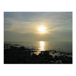 Sunset over rocky coast postcard