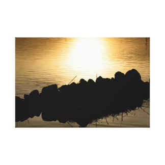 Sunset reflected in calm water and back lit rocks canvas print