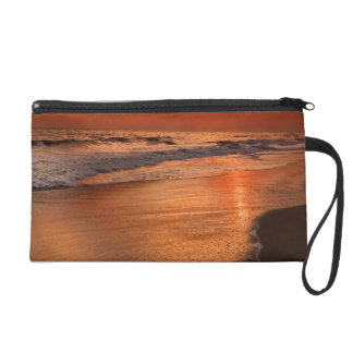 Sunset reflections off clouds and ocean shore wristlet purse