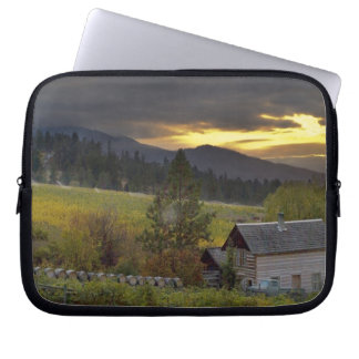 Sunset sky over vineyards and historic log cabin laptop sleeve