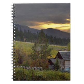 Sunset sky over vineyards and historic log cabin spiral notebook