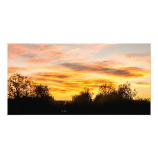 Sunset with cloudy sky behind a hill card