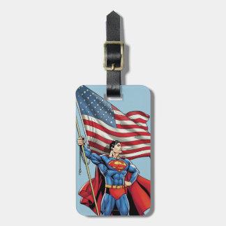 Superhombre que sostiene la bandera de los etiquetas para maletas