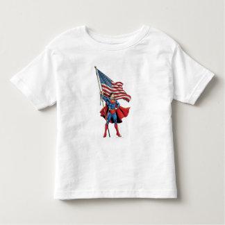 Superhombre que sostiene la bandera de los playera de bebé