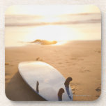 Surfboard laying on beach at sunset drink coasters