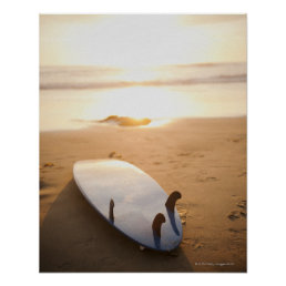 Surfboard laying on beach at sunset poster