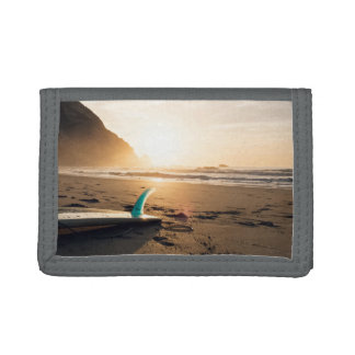 Surfboard lays on the beach as sun appears trifold wallet