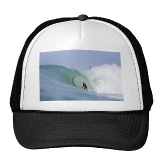 Surfer surfing large blue tropical island wave trucker hat