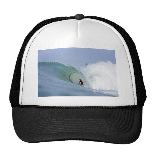 Surfer surfing large blue tropical island wave trucker hat