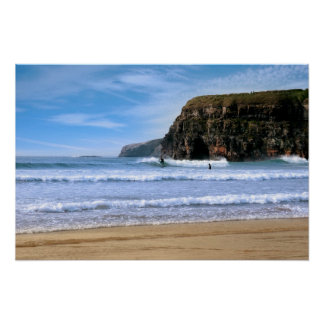 surfers surfing near Ballybunion cliffs Poster
