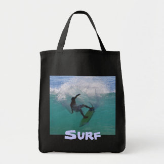 surfing at a big wave tote bag